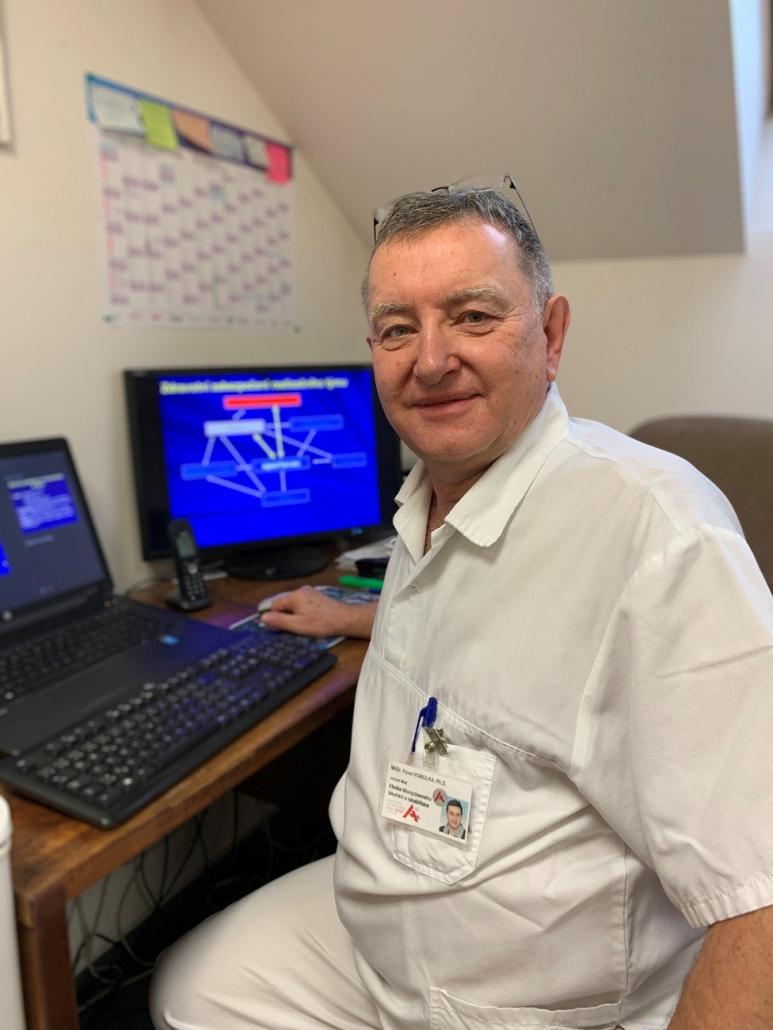 Lékař sedí u počítače.